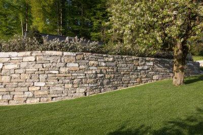 Gepflegter Rasen vor Natursteinmauer