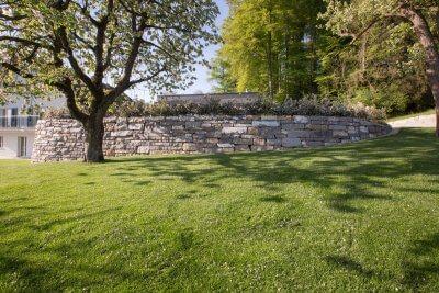 Ebener Platz abgetrennt durch Natursteinmauer
