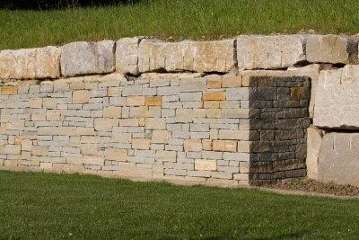 verschieden grosse Natursteinmauern vor Garten