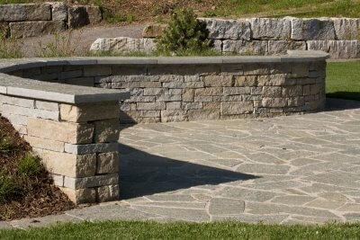 Abgerundete Natursteinmauer mit Deckplattten